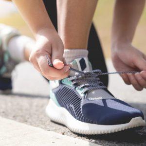 Tu bienestar - Salud - Imagen para artículo de hábitos saludables: corredor atándose los zapatos